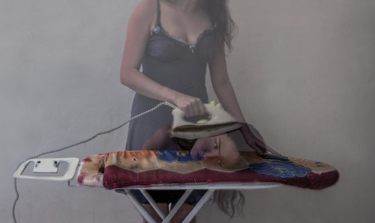 An abstract photograph of a ghost-like female figure ironing. However there is another woman resting her head on the ironing board. And so it appears as if the ghost figure is ironing the woman's face.