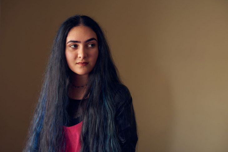 A portrait of Baran Rostamian. She is looking away from the camera and her very long hair is down over her shoulders.