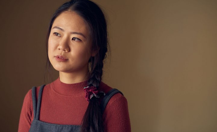 A portrait of Tiffany Ko. Tiffany is wearing a brick-coloured long sleeve top and overalls. She is looking away towards a soft light.