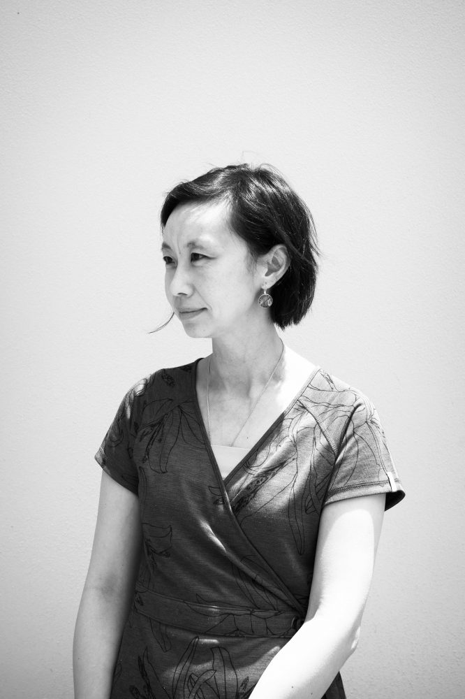 A black and white photo of Emily against a bright orange wall. She is looking off into the distance and is wearing a green dress and green earrings.