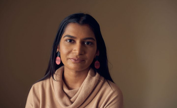 A portrait of Nisha D'cruz. She is looking at the camera and smiling.