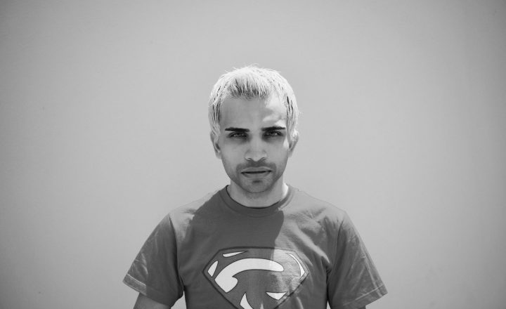 A black and white portrait of Raphael Farmer. He is wearing a superman t-shirt and looking directly at the camera with intense eyes.