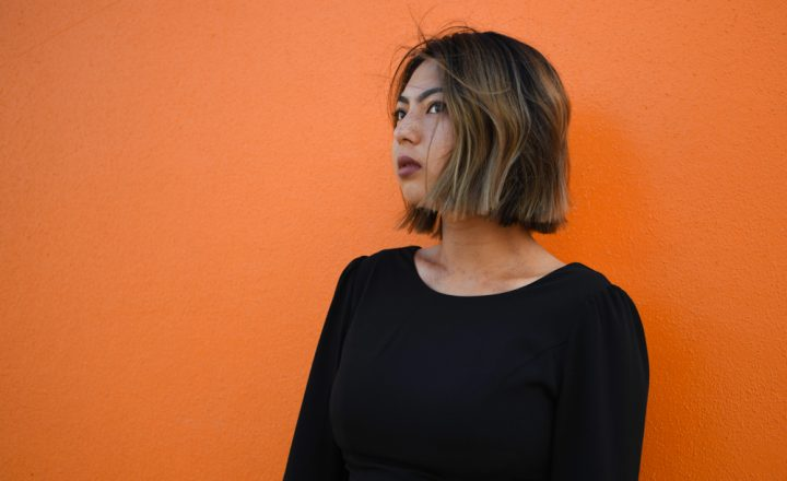 A portrait of Prema Arasu. Prema is photographed against a bright orange wall. They are looking away and the wind is blowing through their hair.