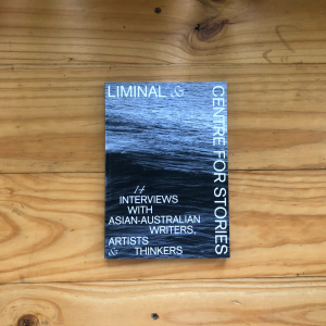 A photograph of a book on top of a light coloured woodern table. The book cover is black and white featuring an image of an ocean and it says 'LIMINAL & CENTRE FOR STORIES Interviews with Asian Australians'