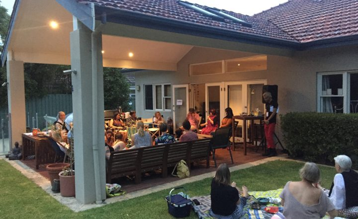Photo of Nedlands Backstories. Many people sit under a patio and on the lawn in the backyard of a house. Three people sit on chairs in front of the audience.