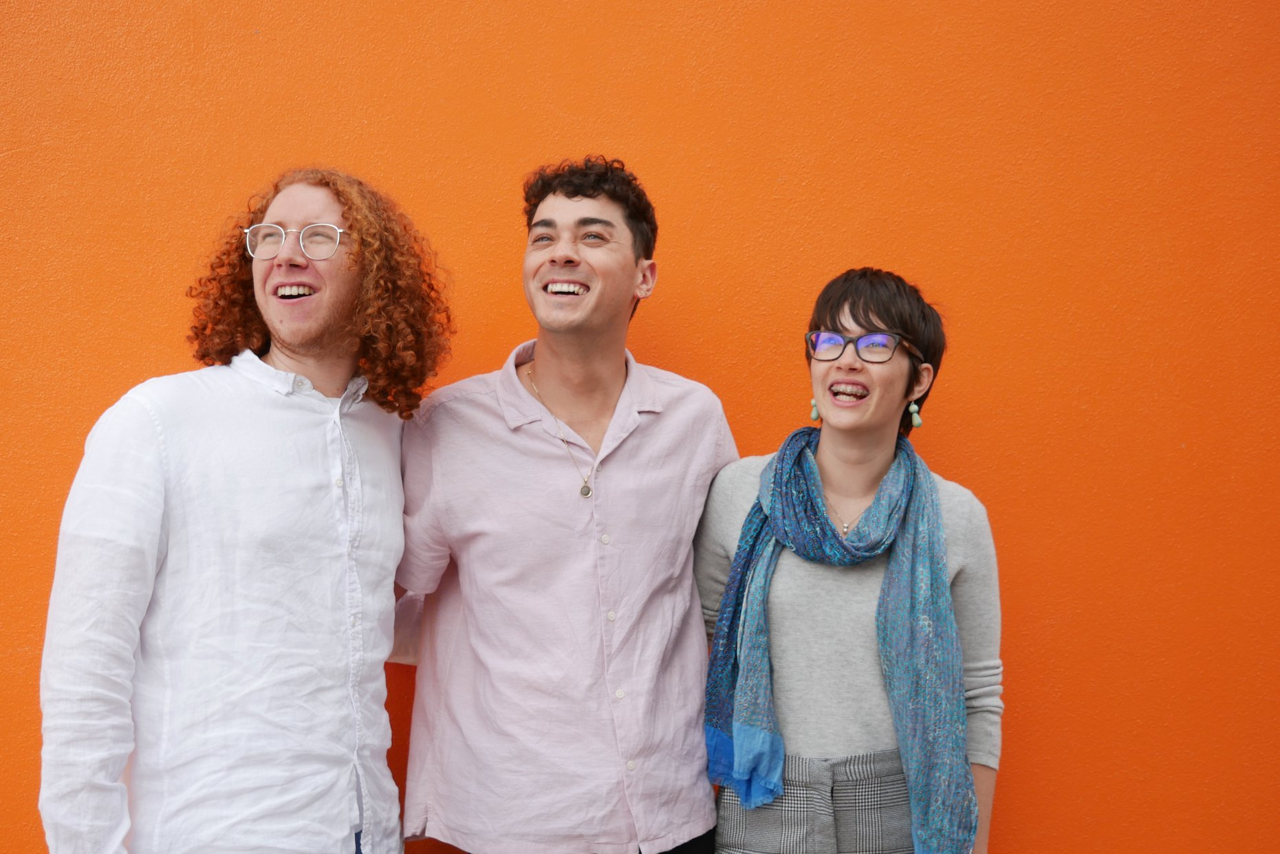 A photograph of three people embracing and smiling. They are all looking past the camera at something to the left. They stand in front of a bright orange wall. The peopple are: Chris Leopardi, Jay Anderson, and Luisa Mitchell