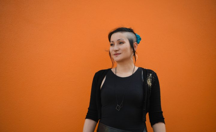 A photograph of Adele Aria standing in front of a bright orange wall. Adele has funky hair and is wearing black.