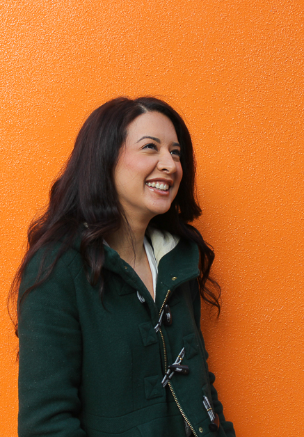 A photograph of Kim Lateef. Kim is standing in front of a bright orange wall and is smiling directly at the camera.