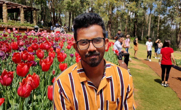 A photograph of Arun sitting beside a bed of tulips and smiling at the camera.