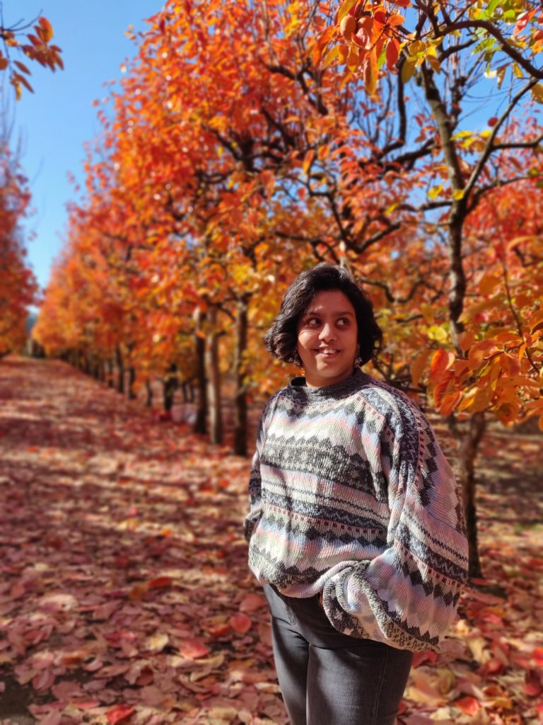 A photograph of Kanchana. They are standing in a beautiful garden of autumn leaves on trees.