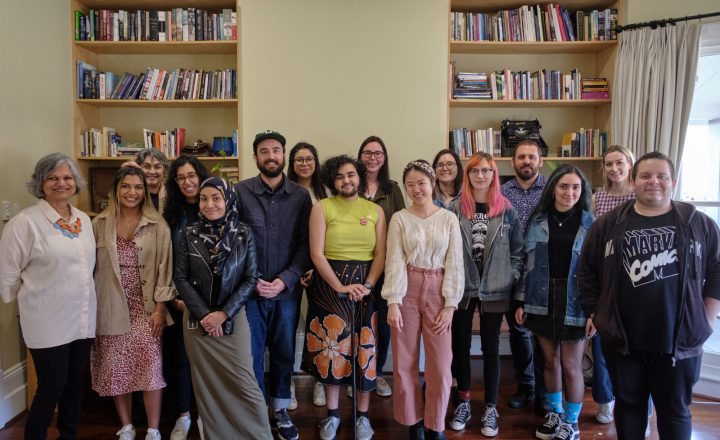 A group photograph of many different people from all walks of life. They are gathered together by a large bookshelf. Each person is smiling and wearing different styles of clothing and self-expression.