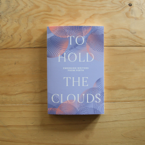 A photograph of a book sitting on top of a light wood table top. The book cover is a soft pastel purple with pink and dark purple cloud patterns layered over each other. The title reads TO HOLD THE CLOUDS in bold white.