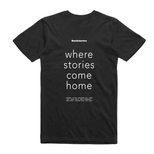 A photograph of a black t-shirt. On the back in big letters across the entire back of the shirt is the slogan 'where stories come home' in sans-serif.