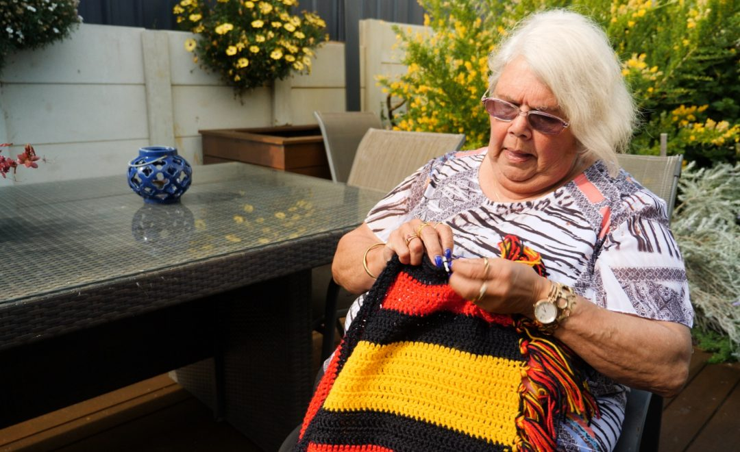 Photo of a woman sitting outside crocheting a blanket that is black, yellow and red.