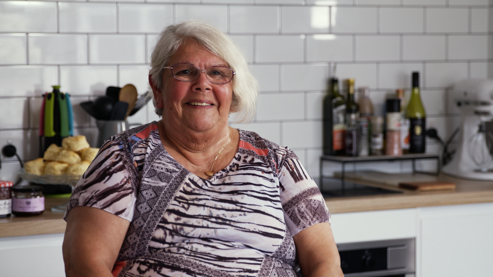 Photo of Doris Hill sitting in a kitchen with white tiles in the background