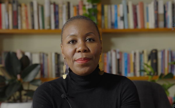 Photo of Sisonke Msimang sitting in front of the book shelves at the Centre for Stories