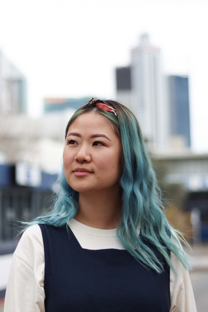 Tiffany Ko is standing looking left into the distance. She has a wistful look on her face. She is standing in front of a building.