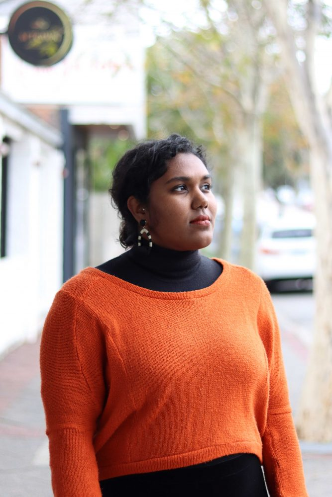 Shenali is standing in front of some buildings and tress. This photo is torso upwards. She is looking off into the distance.