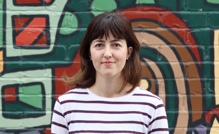 A photograph of Nadia. She is wearing a stripy top and the background is a graffiti wall.